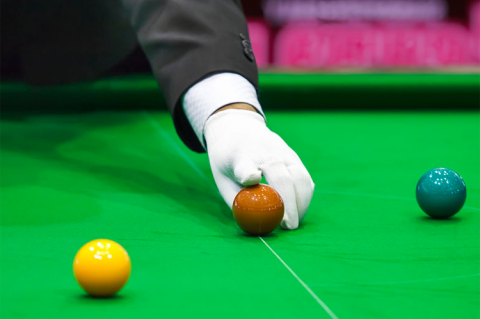 Adjusting snooker ball on snooker table